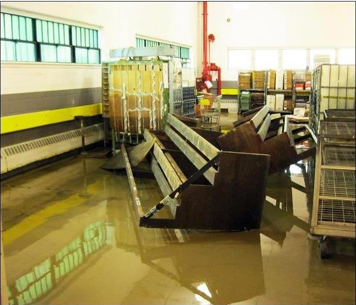 dirty floodwater moved about warehouse equipment and racks