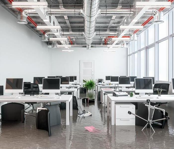 Office with lines of desks with water covering the floor
