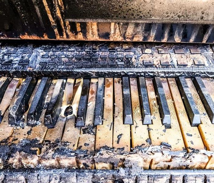 Piano with soot and fire damage on the keys of the piano.