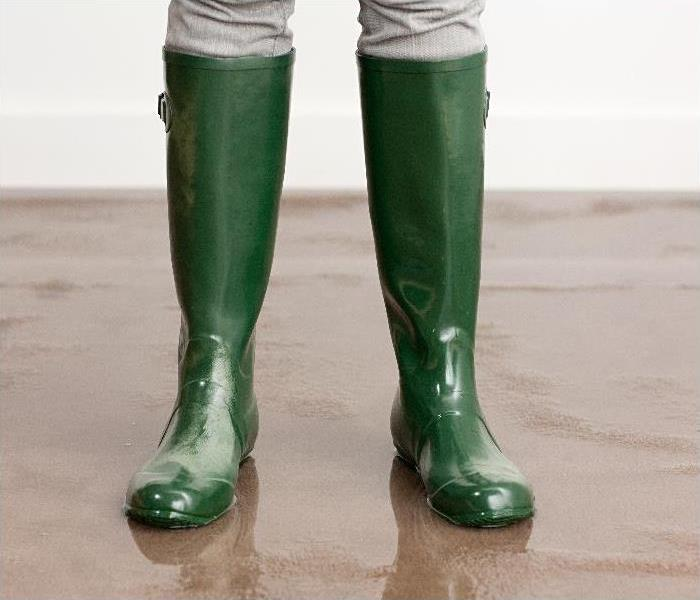 Woman in wellington boots on flooded floor