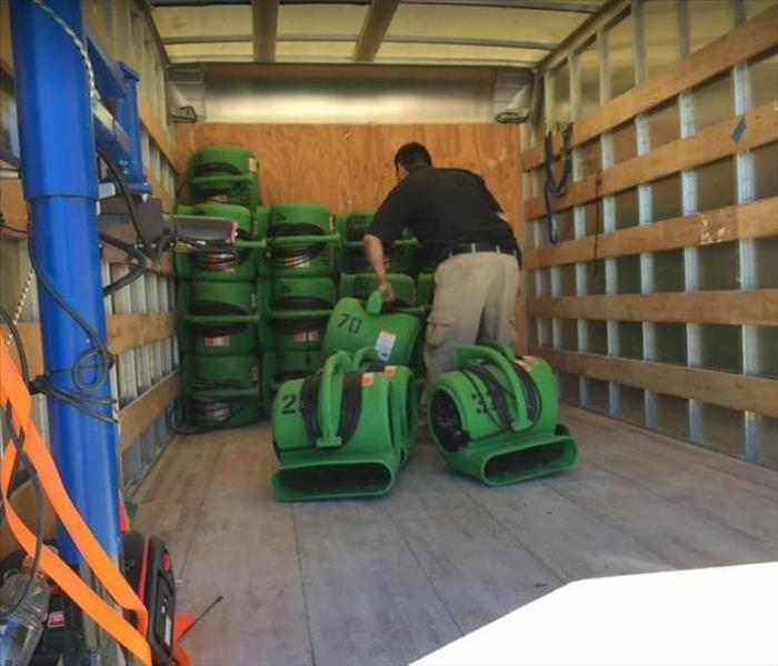 SERVPRO technician loading restoration equipment into SERVPRO vehicle