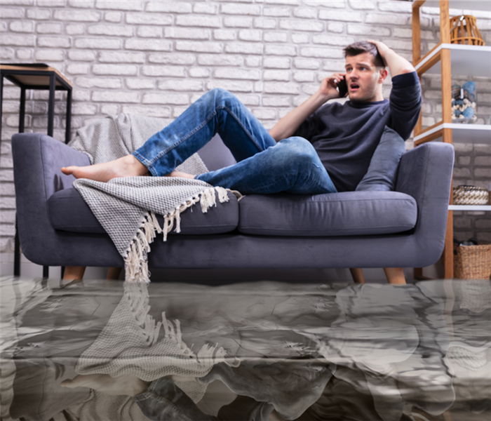 guy sitting on couch in middle of water damaged living room